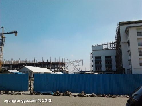 ada pagar pembatas, dibaliknya ada beberapa bangunan gedung yang sedang dibangun. ada celah! yuk intip~