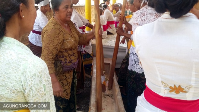 ibu-ibu memainkan musik dengan alu dan lesung