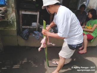 Aji Putu sedang mempersiapkan ayam untuk dibakar